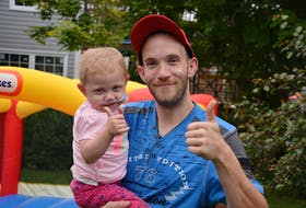 Eddie Fowlow and his daughter, Lexi, pose for a photo in the backyard of their Coley's Point home on Thursday afternoon. A call for donations recently has helped Eddie get a new car to help his family.