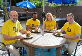 Ron Maynard, president P.E.I. Federation of Agriculture (far left) enjoys a burger with The Old Triangle chef George Joseph (second from left), president and creative director of Fresh Media Melody Dover and Agriculture and Land Minister Bloyce Thompson.
