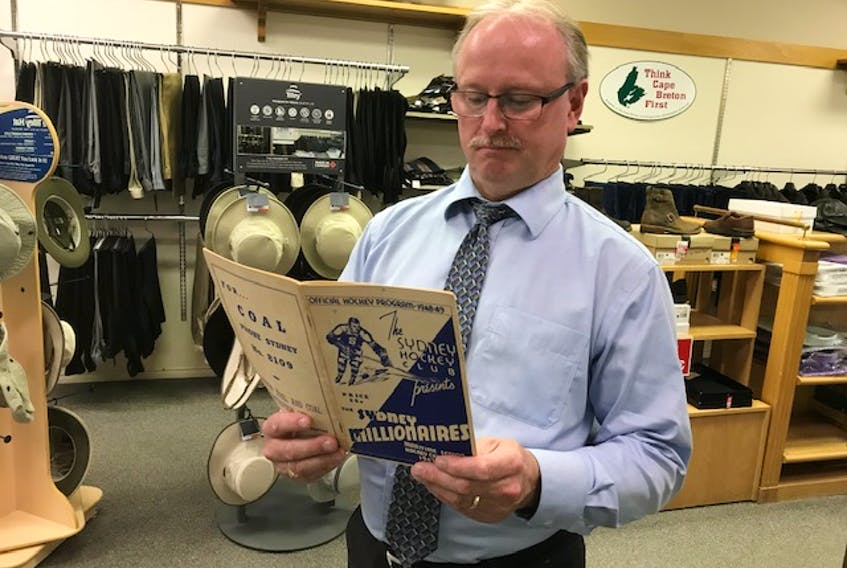 Scott MacVicar, fourth generation owner of Spinner's Men's Wear in downtown Sydney, looks over the Sydney Millionaires program in his downtown store. Contributed • Paul MacDougall