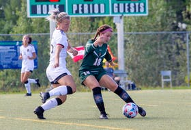 Victoria Miller of the Cape Breton Capers, right, protects the ball as she's pressured by  Jesse Bellamy of the New Brunswick Reds during Atlantic University Sport women's soccer action at Willie O'Ree Place Complex in Fredericton. Cape Breton won the game 5-0. PHOTO CONTRIBUTED/JAMES WEST, UNB ATHLETICS.