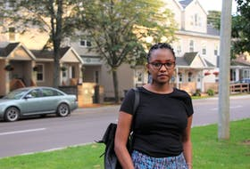 Flossie Mbiriri stands around the corner from the apartment building where she paid $100 to stay one night.