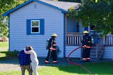 People embrace outside a home on Three Mile Plains Cross Road as firefighters work to extinguish an electrical fire that started in a home office on Sept. 20.