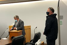 Todd Gillingham (right) waits for his lawyer, Jason Edwards, before leaving a St. John's courtroom Monday morning. Gillingham pleaded guilty to a number of charges and will be back in court in March for sentencing.