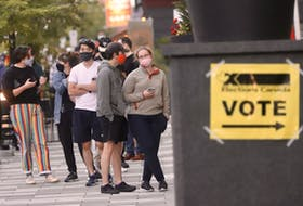 Voters line up to cast their ballots outside a polling station at the convention centre in downtown Halifax early Monday evening, Sept. 20, 2021.