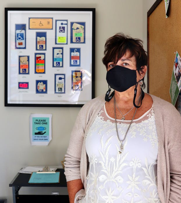 Marcia Carrol, Executive Director of the PEI Council of Persons with Disabilities, stands in front of a display showing accessible parking labels over the years.  - Logan MacLean • The Guardian