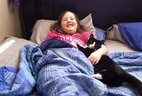 Caitlyn Landry, 11, of Rockdale, Richmond County, relaxing with her cat Sparkles at an earlier date. Father Scott Landry said he is devastated and angry after trusting the Forget Me Not Animal Rescue Society to have his family's beloved cat of eight years spayed and then the society ended up having her euthanized. CONTRIBUTED