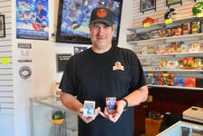 Light The Lamp Sports Card shop owner Gordon Woodill displays some of the wares available at his new business that is located on Charlotte Street in Sydney. DAVID JALA/CAPE BRETON POST
