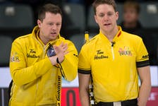 Third stone Adam Casey, right, chats with skip Jason Gunnlaugson during the 2021 Tim Hortons Brier Canadian men's curling championship in Calgary, Alta.