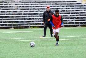 As head coach Jake Stanford (left) looks on, Memorial Sea-Hawks first-year soccer player Emmanuel Dolo moves the ball down the field during a recent practice at King George V Park in St. John's.