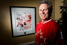 Canadian  hockey hero Paul Henderson  stands beside a painting of his famous goal to beat Team Russia in 1972. Postmedia