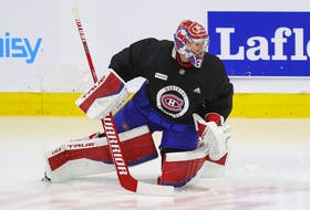 Montreal Canadiens' Carey Price does some exercises on the ice under the supervision of a member of the team's training staff at the Bell Sports Complex in Brossard on Sept. 16, 2021.  Price had off-season knee surgery.