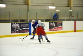 Isaac Wilson carries the puck and looks to make a move on defenceman Sid McNeill during the Summerside Western Capitals' training camp at Credit Union Place's IcePad last week.