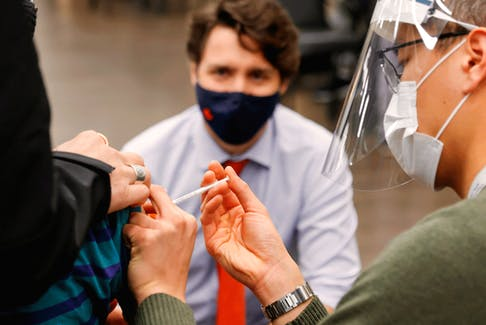 Prime Minister Justin Trudeau watches as a nurse gives a COVID-19 vaccination at a clinic in Ottawa, March 30, 2021.
