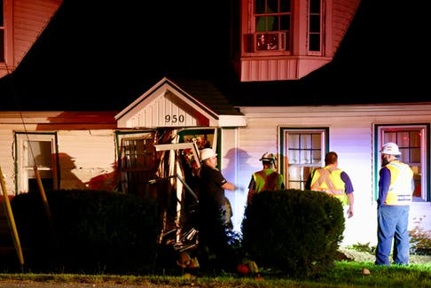 West Hants building inspector Tim Leslie (far left) joined Windsor firefighters outside a King Street duplex that sustained significant damage when a motorist hit it Sept. 21.