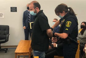 Justin Shane Parsons arrives in a provincial courtroom in St. John's Wednesday afternoon escorted by a sheriff. Parsons was among four people arrested Wednesday in connection with RCMP Project Barnacle and charged with drug trafficking offences.
