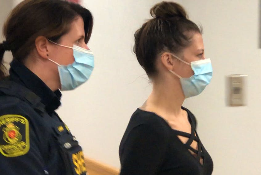 A sheriff escorts Katie Marie Tucker into a provincial courtroom in St. John's, where she was officially charged with nine offences related to illegal drugs and weapons as part of RCMP Project Barnacle.