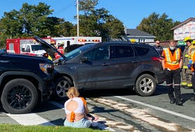 A woman involved in a three-car collision in Mount Pearl on Thursday, Sept. 23, 2021, sits on the curb with her infant child.