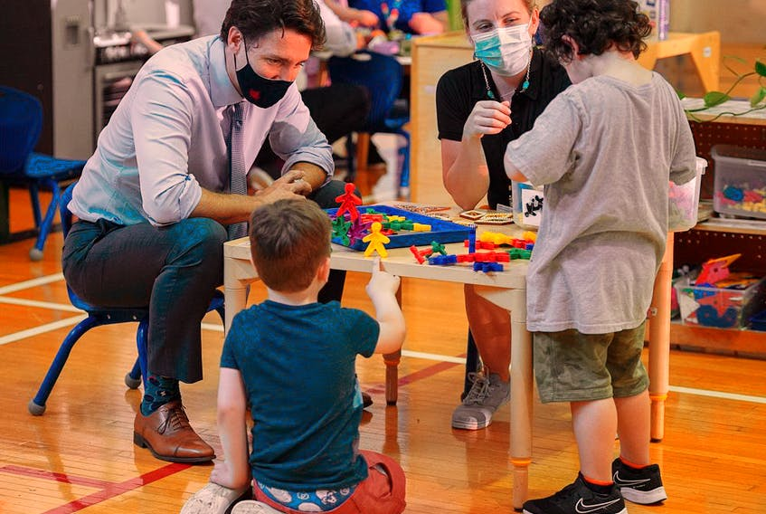 Prime Minister Justin Trudeau visits children at a daycare in St. John's, N.L. in July. The province struck a deal with Ottawa for a $10-a-day child-care program.