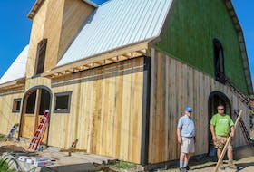 Chris Gorey, left, and Ryan Costelo, right, stand in front of the partially rebuilt Groovy Goat Farm & Soap Company's barn, in Ingonish on Wednesday. The Groovy Goat has been rebuilding its barn following the loss of the original, which housed goats, horses and chickens, to a massive fire in late February 2021. The company, owned by Ryan and Shannon Costelo, began a community-driven rebuild in late July and have been working on it ever since. JESSICA SMITH/CAPE BRETON POST