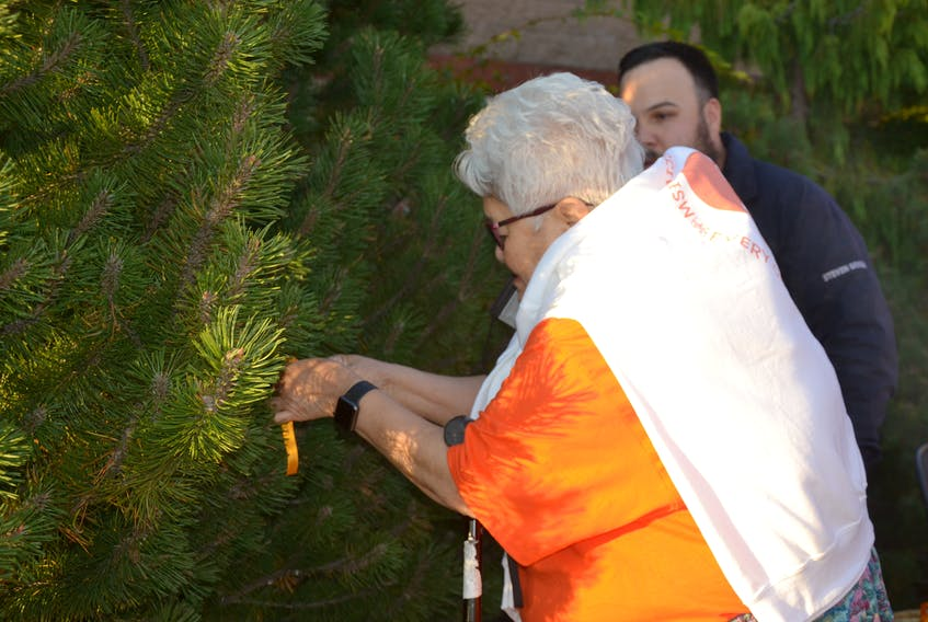 Katie McEwan, an elder and residential school survivor from Membertou, ties the first orange ribbon to the Tree of Rememberance outside the Port Hawkesbury Civic Centre as Coun. Steven Googoo from We'koqma'q looks on. ARDELLE REYNOLDS/CAPE BRETON POST