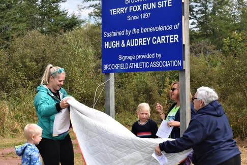 Taking part in the unveiling of the sign honouring the late Hugh and Audrey Carter were the couple's granddaughter-in-law Christina Lutes (left) with her children and their great-grandchildren Eli and Audrey, as well as Terry Fox Run committee members Kim Dawe and Judy Matheson.