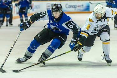 Saint John Sea Dogs forward Cam MacDonald, left, shields the puck from Cape Breton Eagles defenceman Jarrett Baker during a 2020-21 QMJHL game. - QMJHL