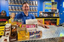 Corey Lynch poses in his St. John's basement — yes, his basement. The longtime film buff and movie memorabilia collector has transformed his rec room into Megahit Video, technically a fictional video rental store but very much an online experience.