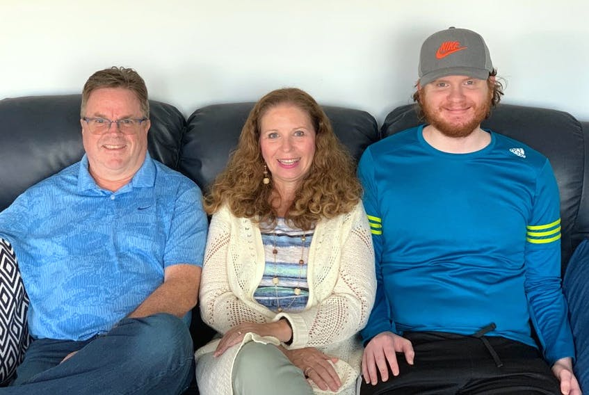Kyle MacLean, right, sits with his mother Joanne Lawrence-Phalen and stepfather John Phalen. The Glace Bay man's family and friends have been a big support to him over the past two years as he fought to find out what was wrong with him and continue to do so as he starts fighting to get coverage for needed spinal surgeries. CONTRIBUTED
