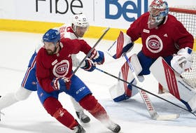 Canadiens' Xavier Oullet, left, battles with Ryan Poehling in front of goaltender Cayden Primeau during training camp Thursday in Brossard.