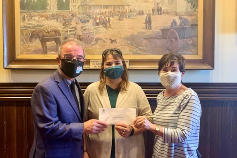 Mayor Philip Brown presents gift certificates to Judy Skerry (middle) and Carol Smith, who accepted the prize on behalf of the volunteers who worked in the gardens at the Holy Redeemer Catholic Parish Church--the winner of the 2021 Mayor's Award in the city's Make Our Hometown Beautiful program.