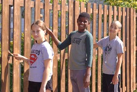 Three of the Hard Workers Youth Service Co-op worker-members shown, from left, Lily Gagnon, Robert Ondoua and Jaxon Short, clean and repaint a large fence at the back of the Évangéline-Central Credit Union in Wellington over the summer. The co-op recently finished its summer of work, with members generating a small profit after salaries and expenses.