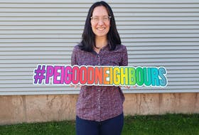Lindee Gallant holds up a sign with hashtag #PEIGoodNeighbours. She encourages people across the Island to share stories of neighbours' good deeds using this hashtag.