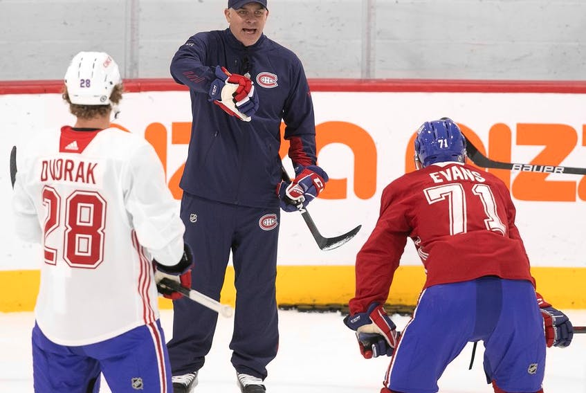 Christian Dvorak and Jake Evans listen as head coach Dominique Ducharme gives instructions during Canadiens training camp Friday at the Bell Sports Complex in Brossard.