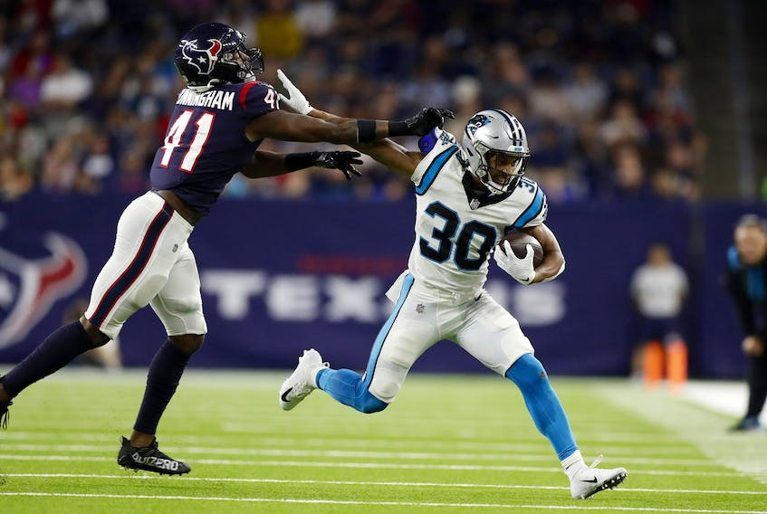 Chuba Hubbard of the Carolina Panthers tries to hold off the tackle of Zach Cunningham of the Houston Texans last week.