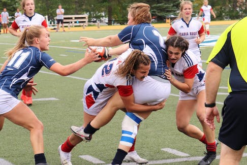St. Francis Xavier's Claudia Fulton is tackled by two Acadia players during an Atlantic university rugby match Saturday afternoon in Antigonish. The first-place Axewomen won 38-31 to improve to 3-0. - SYDNEY HAWS