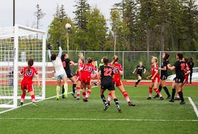 A corner kick by Cape Breton rookie Paige Allaby flies into the net above Acadia keeper Milena Ramirez. The game-tying goal was one for the ages as Allaby, shown in the background facing the camera, kicked it high toward the top of the penalty box and the strong wind amazingly carried the ball over everybody and into the back of net. The Sunday afternoon match between the host Capers and the visiting Axewomen ended in a 1-1 draw. DAVID JALA/CAPE BRETON POST
