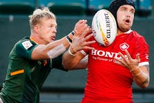 Canada's Jake Thiel, right, battles for the ball against South Africa's J.C. Pretorius during HSBC Canada Sevens rugby action in Edmonton on Saturday, Sept. 25, 2021.