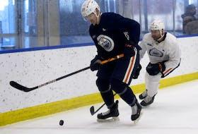 Adam Cracknell (27) battles Ryan Stanton (5) during an Edmonton Oilers training camp scrimmage, in Edmonton Thursday Jan. 7, 2021.