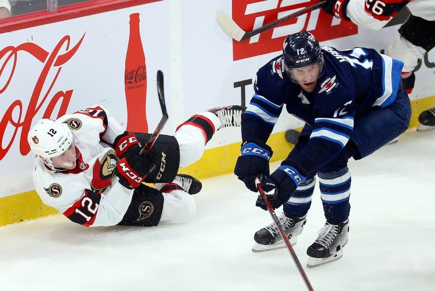 Ottawa Senators forward Shane Pinto clears the puck from his backside with Winnipeg Jets forward Jansen Harkins closing in on Sunday.