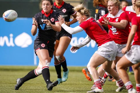 anada's Alysha Corrigan, front left, passes the ball as Britain's Megan Jones grabs her during a women's HSBC Canada Sevens rugby match in Edmonton on Sept. 25, 2021.