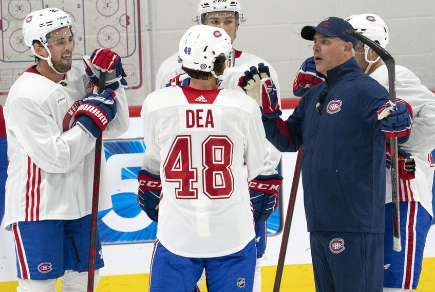 Montreal Canadiens head coach Dominique Ducharme speaks to Chris Wideman, left Joshua Roy and Jean-Sébastien Dea  during training camp  on Sept. 23, 2021, in Brossard.