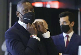 Raptors Masai Ujiri, vice-chairman and president of the team, and general manager Bobby Webster (R) stand at the back of the press conference on media day at the Scotiabank Arena.