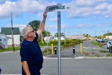 Coal Town Trail Society member Allister MacLean checks out the damage to a recently-erected street sign in the downtown Glace Bay section of the 15-km trail that connects Gardiner Mines with Tower Road. MacLean said a stop sign affixed to the pole was ripped off and has not been recovered. DAVID JALA/CAPE BRETON POST