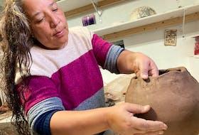 Eskasoni potter Nancy Oakley working on a traditional Mi'kmaq cooking pot.