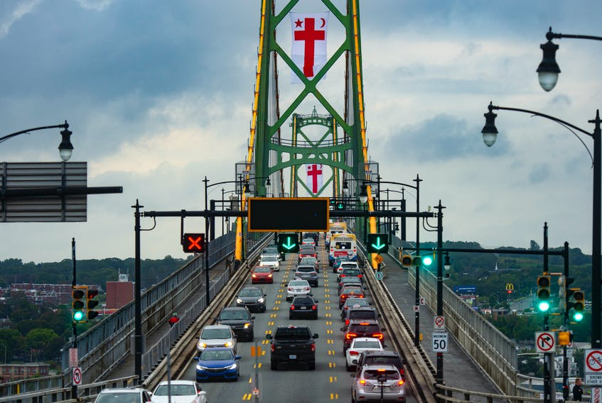 Vehicles pass over the Macdonald Bridge as Mi'kmaq Grand Council flags fly from the bridge towers in recognition of Thursday's National Day for Truth and Reconciliation on Tuesday, Sept. 28, 2021.