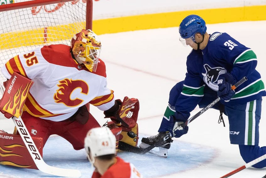 Calgary Flames goalie Adam Werner (35) stops Vancouver Canucks' Alex Chiasson (39) during the first period of a pre-season NHL hockey game in Abbotsford, B.C., Monday, Sept. 27, 2021.