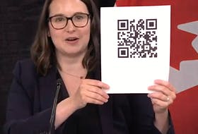 Digital Government Minister Sarah Stoodley shows what a QR code looks like during a news briefing in St. John's Tuesday.