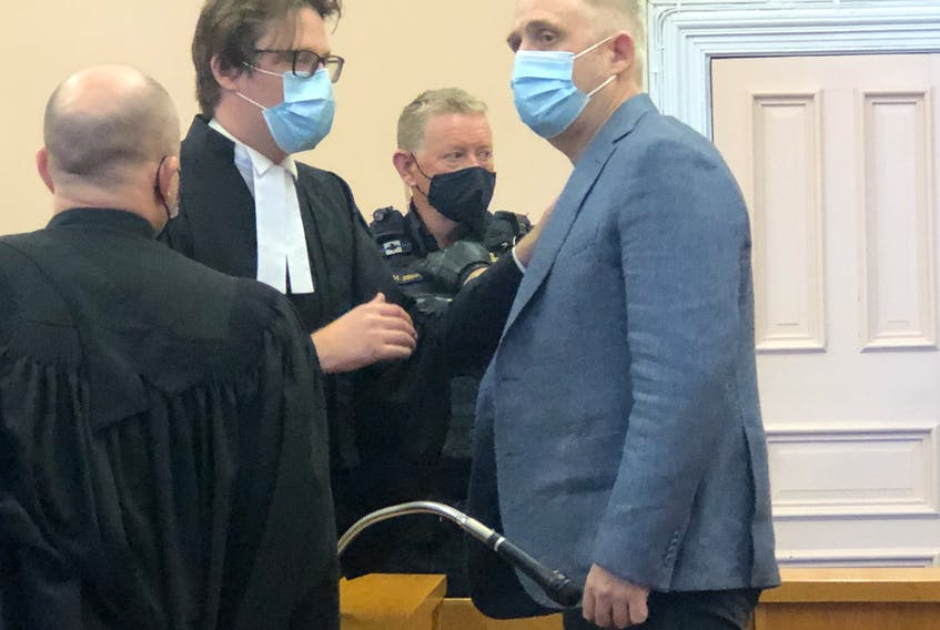 Kurt Churchill (right) speaks with James Foy (wearing glasses) and Robby Ash, two of the three lawyers representing him at his bail hearing in Newfoundland and Labrador Supreme Court in St. John's Tuesday.