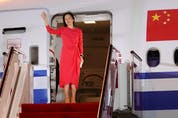 Huawei Technologies Chief Financial Officer Meng Wanzhou waves as she steps out of a charter plane at Shenzhen Baoan International Airport in Shenzhen, Guangdong Province, China, Sept. 25, 2021.