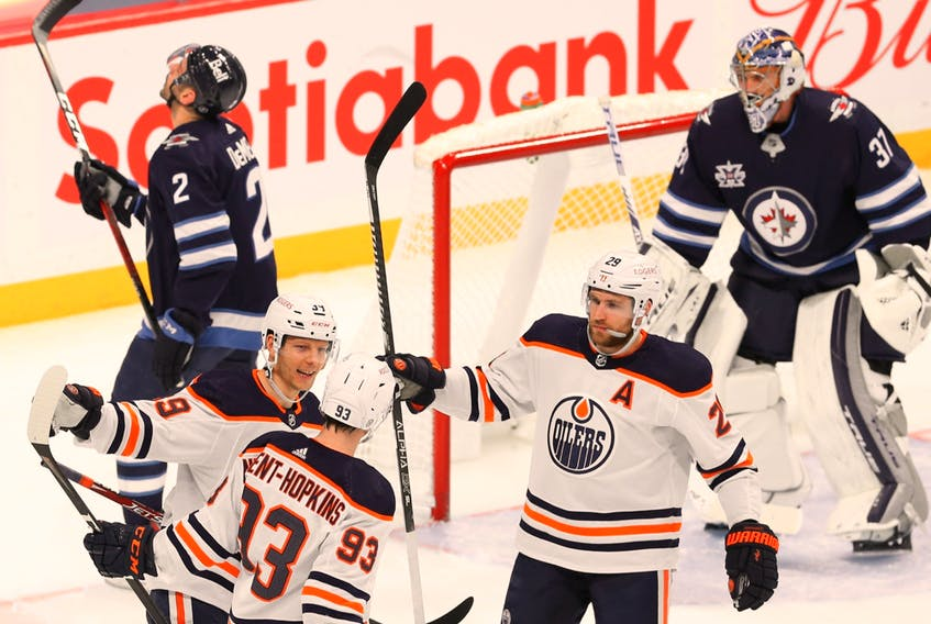 Edmonton Oilers forward Ryan Nugent-Hopkins (93) celebrates his second-period, power-play goal with Alex Chiasson (left) and Leon Draisaitl in Winnipeg on April 27, 2021.